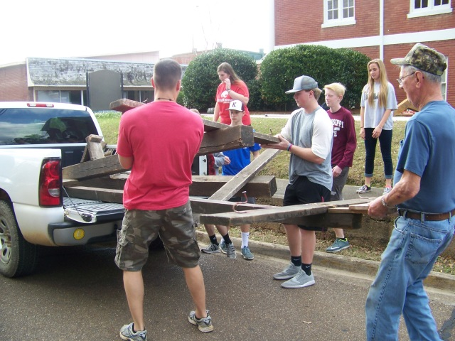 Youth and adults unload crosses to place on the Cavalry set.